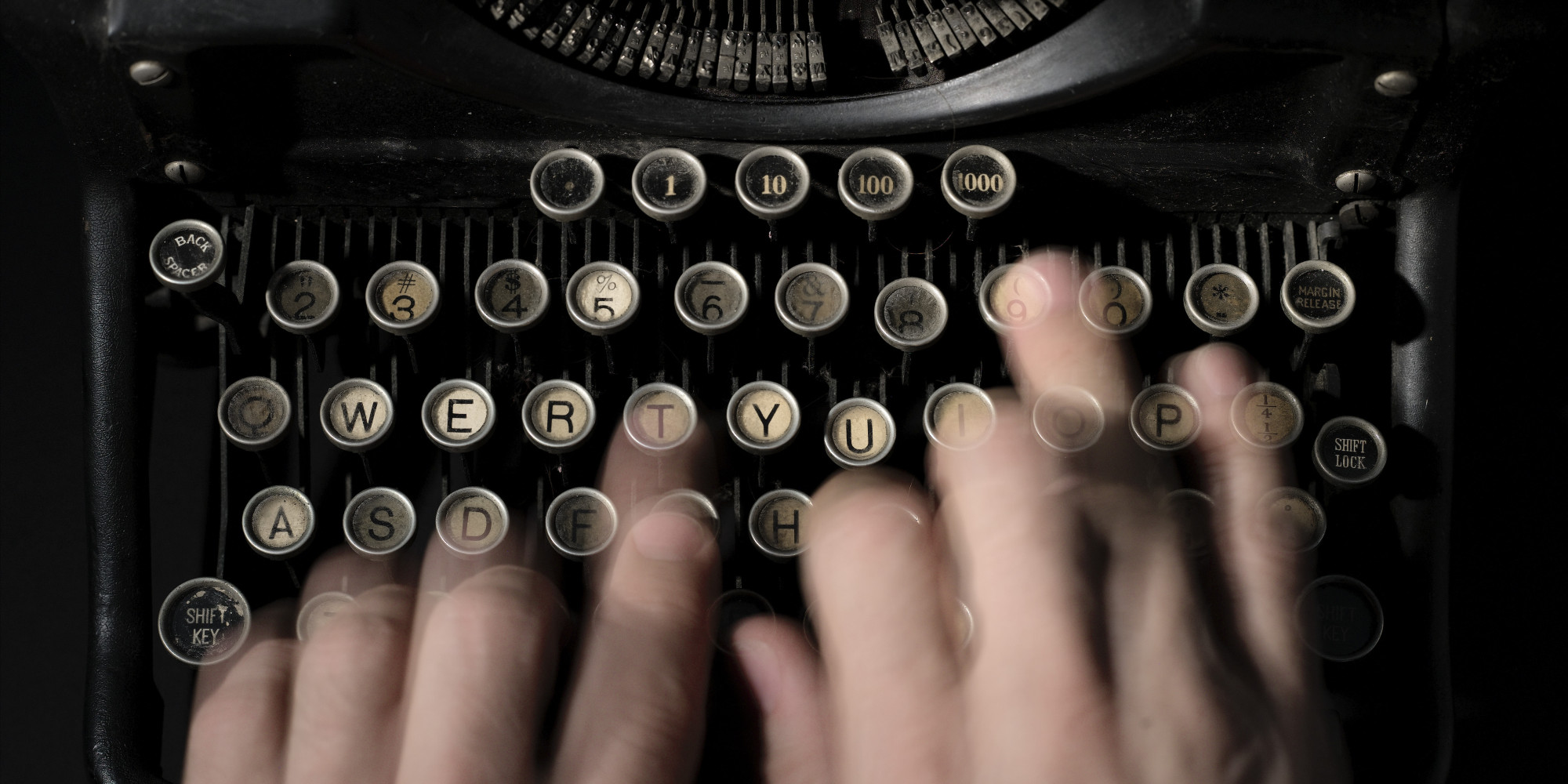 Person typing on manual typewriter, close-up (blurred motion)