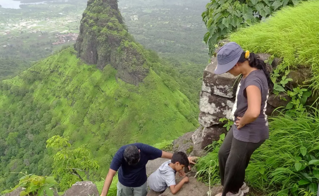 A family climbs to the top of Gorkhagad with Machirgad in the background